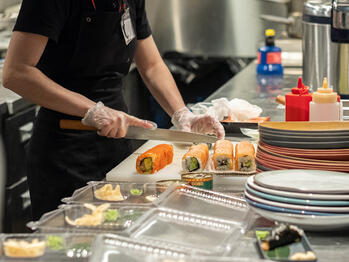 Kitchen staff preparing sushi for delivery or takeaway