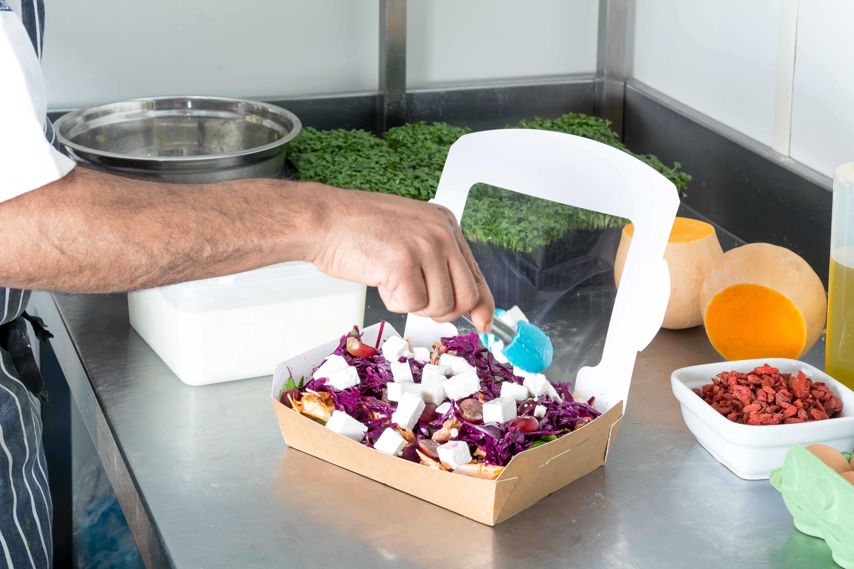 Hand of chef preparing to go box salad