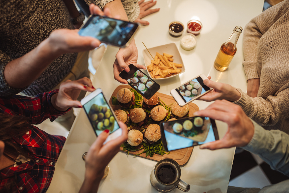 Friends taking food photos for social media