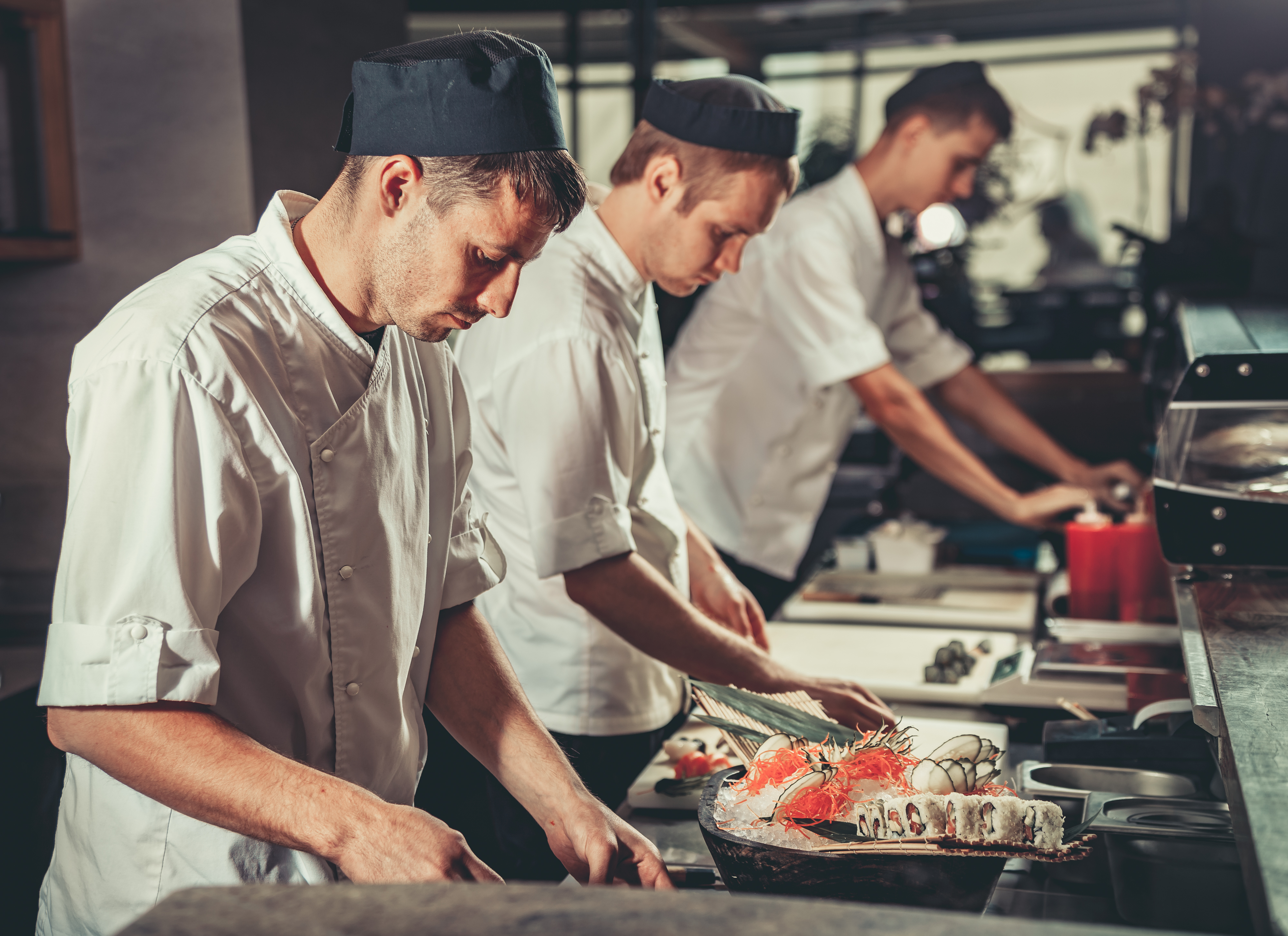 Chefs preparing sushi in kitchen